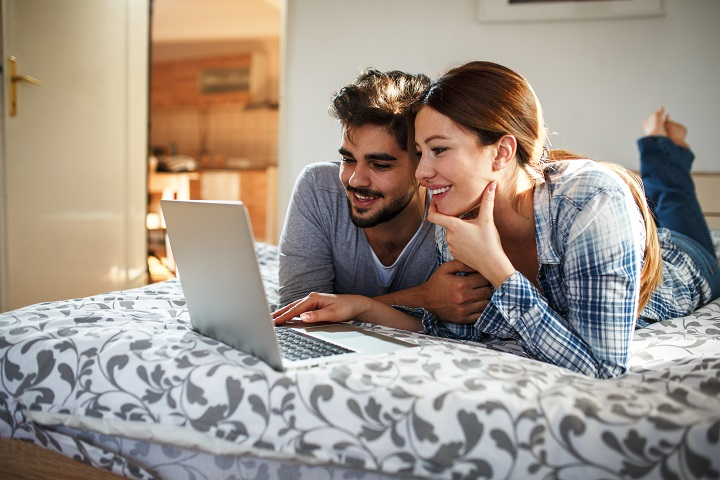Young married couple lying on bed at home and using laptop.