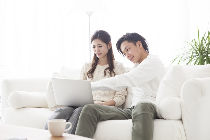 Young couple looking at a laptop in the living room